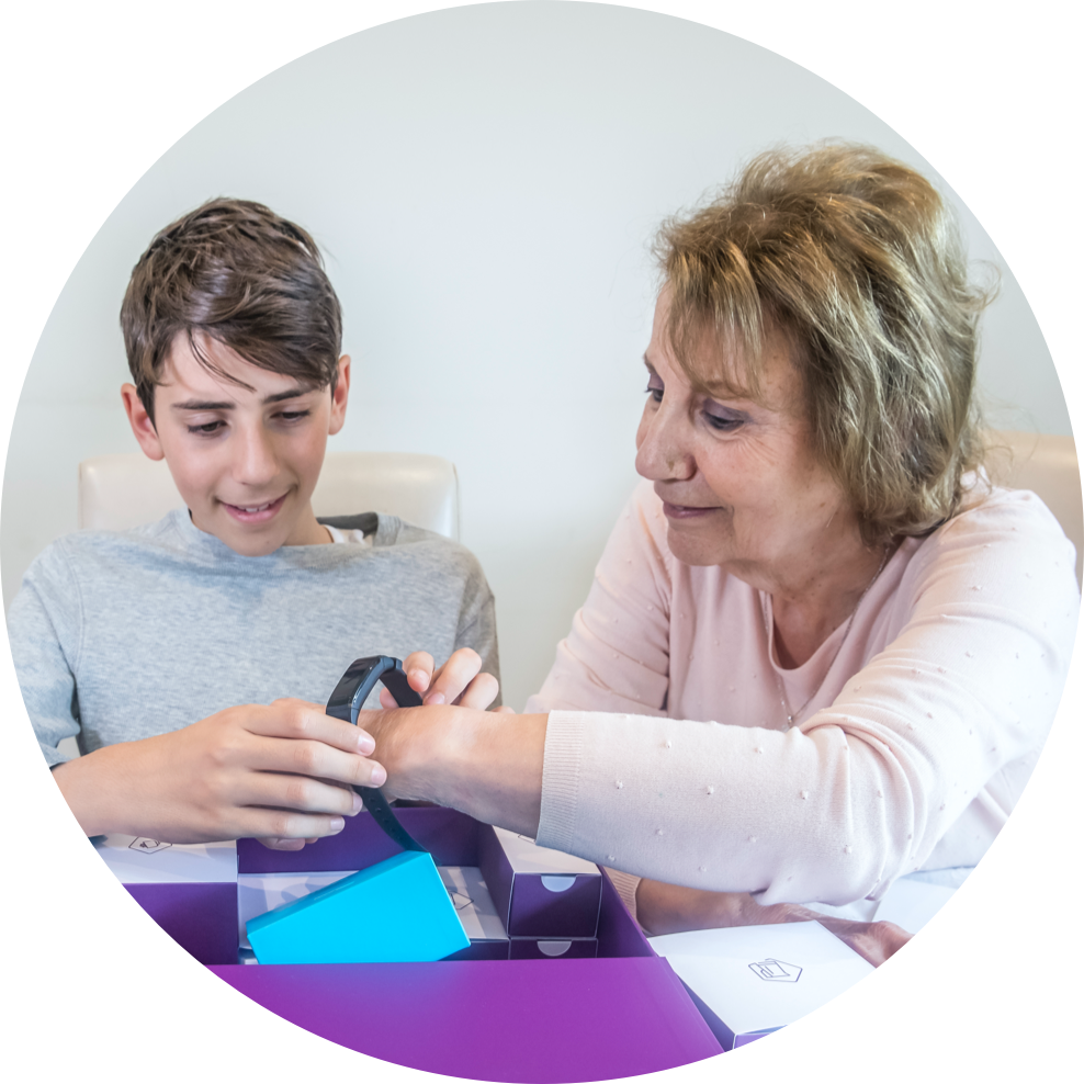 A Boy Helping His Grandmother With A Wearable Sensor