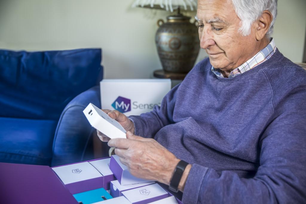 An older man opening a new MySense Sensor Kit